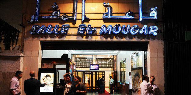 Algerians walk outside the Salle el-Mougar during the world premiere of 'Ce que le jour doit à la nuit'...