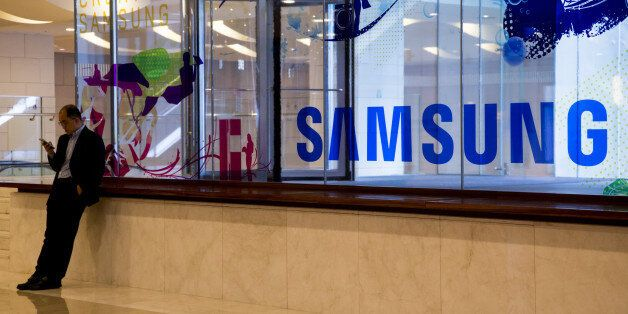 A man uses a mobile device in front of Samsung Electronics Co. signage at the company's D'light flagship...