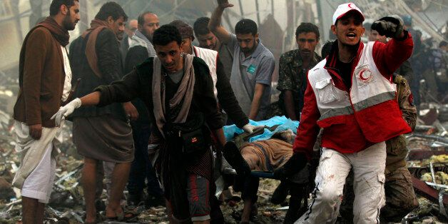 Yemeni rescue workers carry a victim on a stretcher amid the rubble of a destroyed funeral hall building...