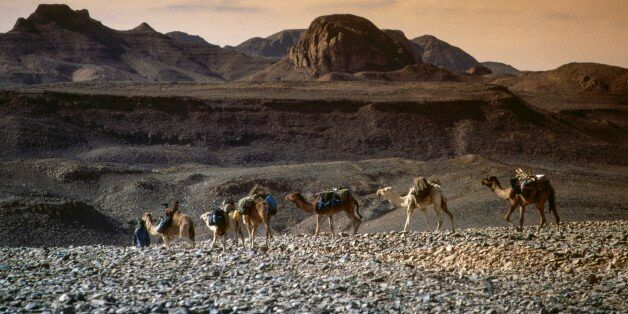 ALGERIA - MARCH 18: Camel caravan, Hoggar Mountains (Ahaggar), mountain range formed from volcanic rocks,...