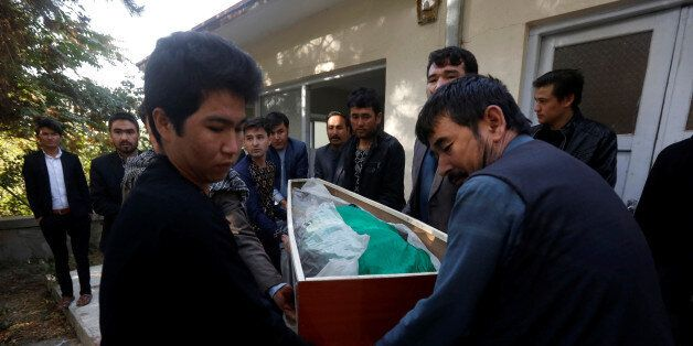 Afghan men carry the dead body of a civilian at a hospital after gunmen attacked a shrine in Kabul, Afghanistan...