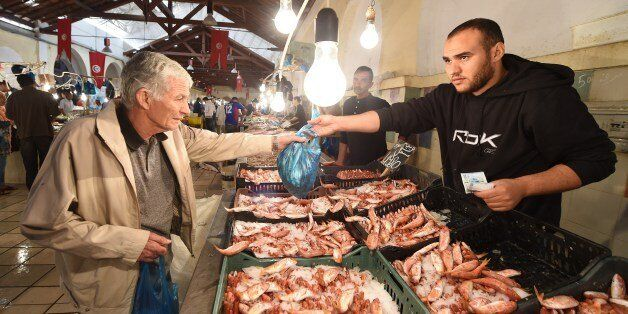 A fish vendor sells his goods to a customer in the central market of Tunisia on October 23, 2014. AFP...