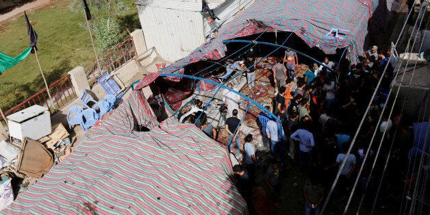 People gather at the site of a suicide bomb attack in the city's northern al-Shaab district in Baghdad,...