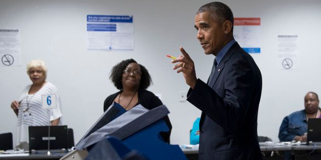 Poll workers look on as US President Barack Obama (C) gestures towards the press as he votes early at...