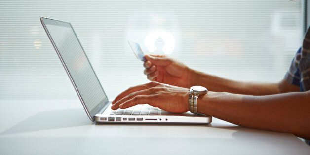 African american male arms hold credit card as he makes an online internet purchase with his laptop computer...