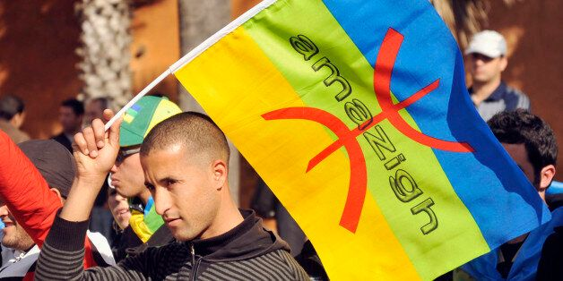 A local Amazigh Berber man waves a Berber flag as he attends a rally calling for the release of political...