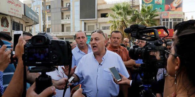 Majed Hattar (C), brother of the Jordanian writer Nahed Hattar, speaks to the media during a sit-in in...