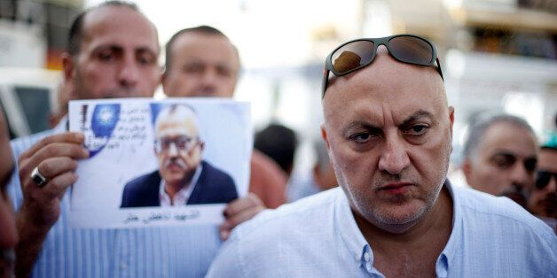 Majed Hattar (R), brother of the Jordanian writer Nahed Hattar, speaks to the media during a sit-in in...