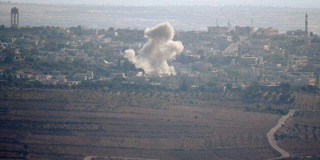 Smoke from explosions rises during fighting in the village of Jubata Al Khashab in Syria, as seen from...