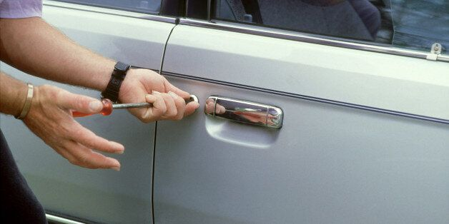 close-up of mans hands using screwdriver to break into