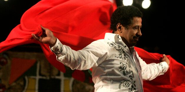 Algerian singer Cheb Khaled covers himself with a Moroccan flag during his concert at the annual Gnaoua...