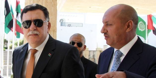 Libyan Prime Minister Fayez al-Sarraj (L) arrives for the second day of UN-brokered talks with members...