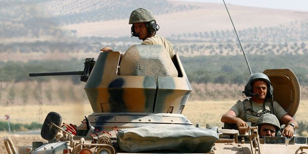 Turkish soldiers on an armoured personnel carrier escort a military convoy on a main road in Karkamis...