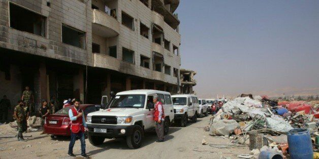 Des ambulances du Croissant rouge escortés par des soldats de l'armée syrienne dans la ville rebelle...