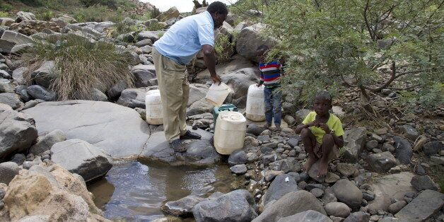 A man and his grandchildren collect water from the Nkuzana River as water to homes has been cut off due...