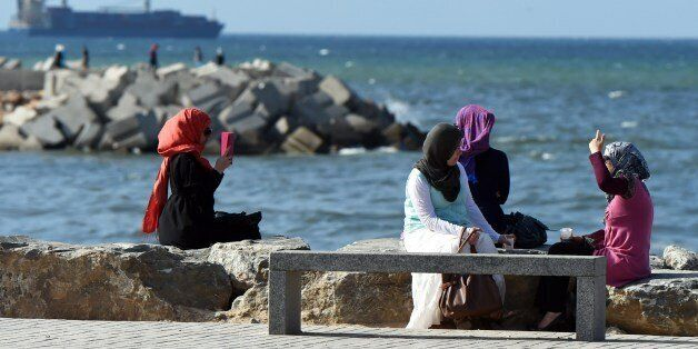 TO GO WITH AFP STORY BY ABDELLAH CHEBALLAHAlgerian women sit on the Sablettes seafront promenade on May...