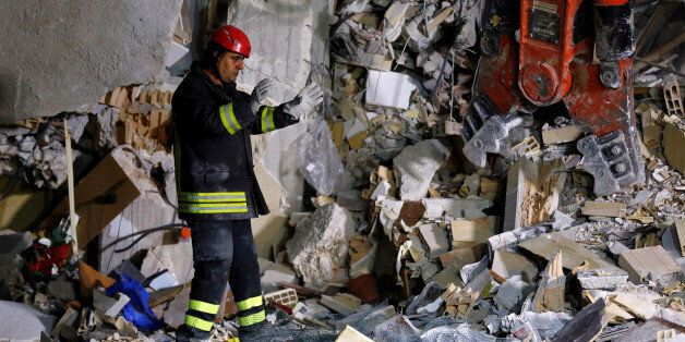 A firefighter works in the night at a collapsed house following an earthquake in Amatrice, central Italy,...