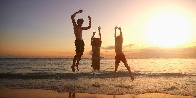 Caucasian children jumping for joy on