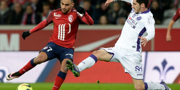 Lille's French midfielder Sofiane Boufal (L) challenges Toulouse's French midfielder Yann Bodiger during...