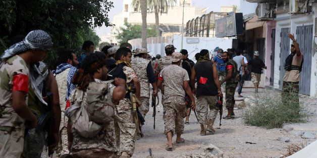 Members of the forces loyal to Libya's UN-backed Government of National Accord (GNA) walk toward their...