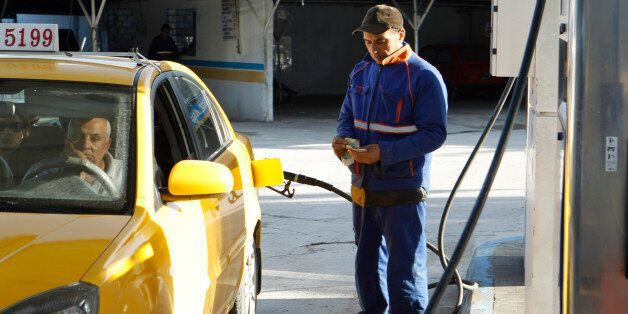 An employee counts money as he fills up a taxi's tank with fuel at a gas station in Tunis March 11, 2013....