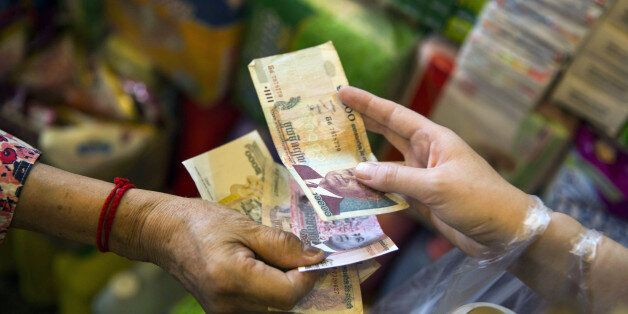 A customer and vendor exchange Cambodian riel banknotes at a market stall in Phnom Penh, Cambodia, on...