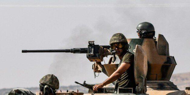 Des soldats turcs dans un tank en route pour la Syrie depuis la ville frontalière turque de