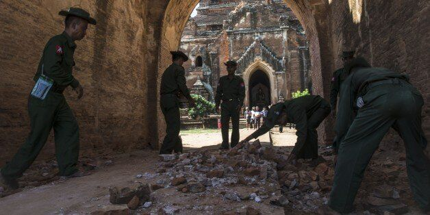 BAGAN, MYANMAR - AUGUST 25 : Myanmar military staff and a police officer collect the pieces of bricks...