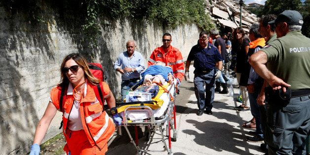 An injured person is carried away on a stretcher following an earthquake at Pescara del Tronto, central...