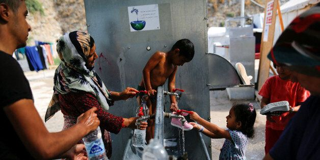 Anis, 4, from Syria (C) is bathed by his mother, as others wash their clothes and shoes, at the Souda...