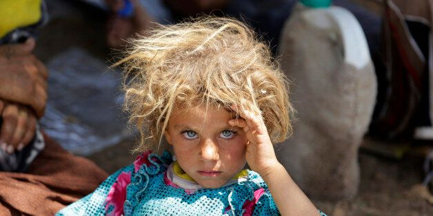 A girl from the minority Yazidi sect, fleeing the violence in the Iraqi town of Sinjar, rests at the...