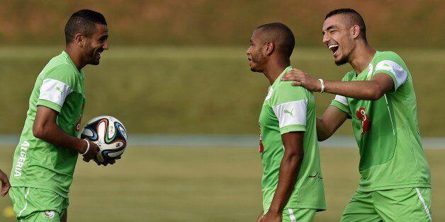 Algeria's midfielder Nabil Bentaleb (R), midfielder Yacine Brahimi (C) and forward Riyad Mahrez (L) joke...