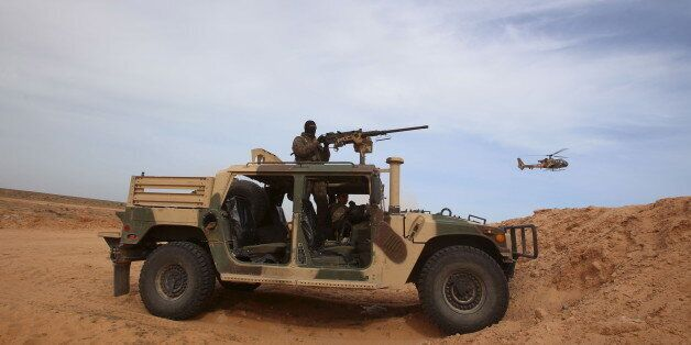 A Tunisian soldier holds his position during an exercise along the frontier with Libya in Sabkeht Alyun,...