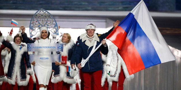 FILE - In this Feb. 7, 2014 file photo Alexander Zubkov of Russia carries the national flag as he leads...