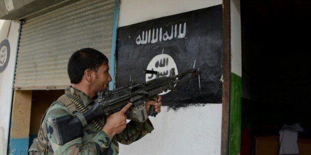 Un soldat de l'armée afghane pointe son arme sur un drapeau de Daech, le 26 juillet 2016 © AFP/Archives...
