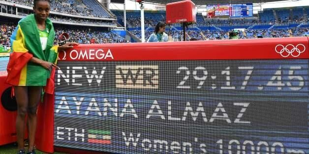 Ethiopia's Almaz Ayana celebrates next to a board displaying her new world record after the Women's 10,000m...