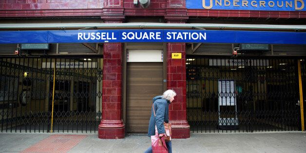 FILE PHOTO - A woman walks past a closed entrance of Russell Square underground station in London April...