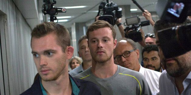 Journalists surround American Olympic swimmers Gunnar Bentz, left, and Jack Conger, center, as they leave...