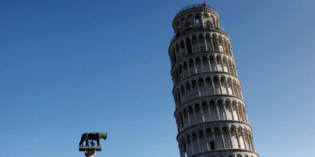 A small sculpture of 'Romulus and Remus' is seen in front of the Leaning Tower of Pisa July 19, 2012....