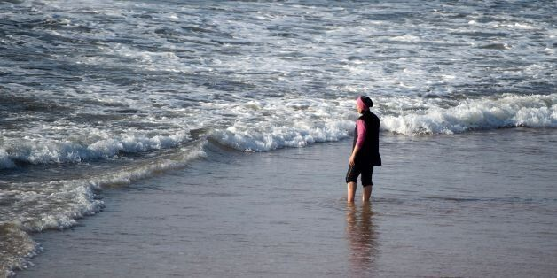 A Moroccan woman wearing a 'burkini', a full-body swimsuit designed for Muslim women, enters the sea...