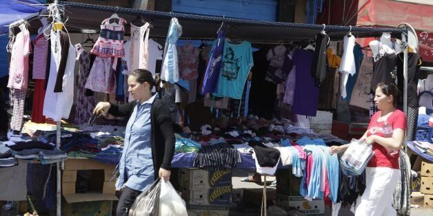 Women walks past a clothing stall during the holy month of Ramadan in the old city of Tunis August 10,...