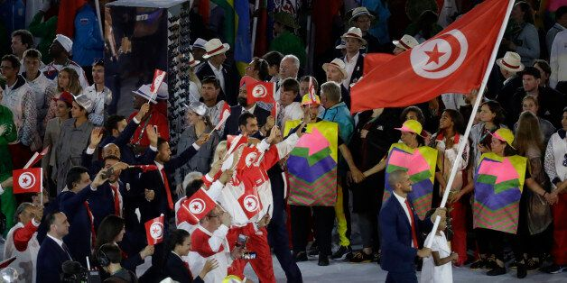 Oussama Mellouli carries the flag of Tunisia during the opening ceremony for the 2016 Summer Olympics...