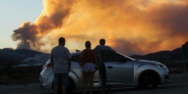 Des gens observent l'incendie de Blue Cut à l'est de Los Angeles, aux Etats-Unis, le 16 août