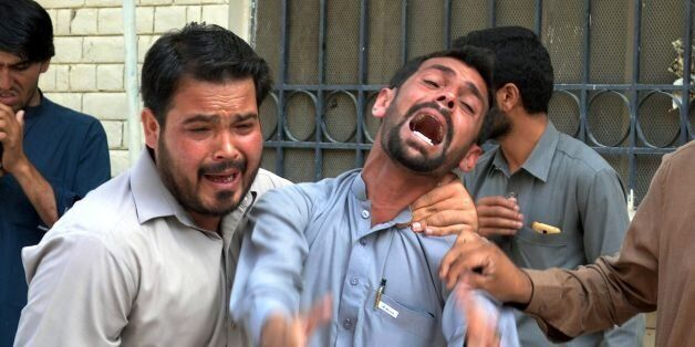 Pakistani bystanders react at the site after a bomb explosion at a government hospital premises in Quetta...