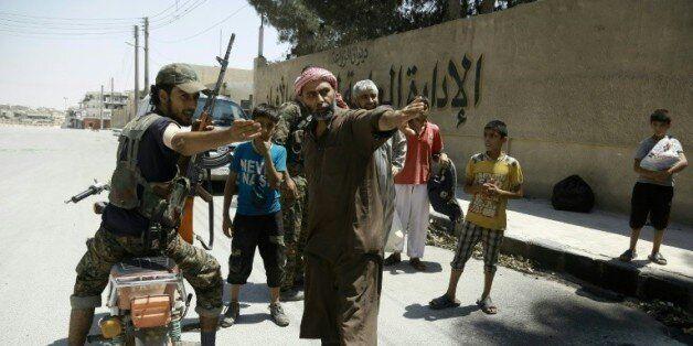 Un membre des Forces démocratiques syriennes (FDS) indique le chemin aux civils fuyant un quartier contrôlé...