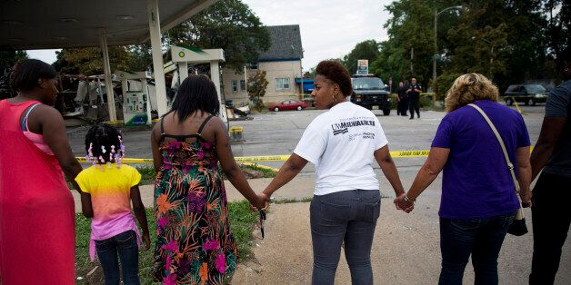 Jasmine Newson, 21, turns around while praying at a gas station that was destroyed by rioters after a...