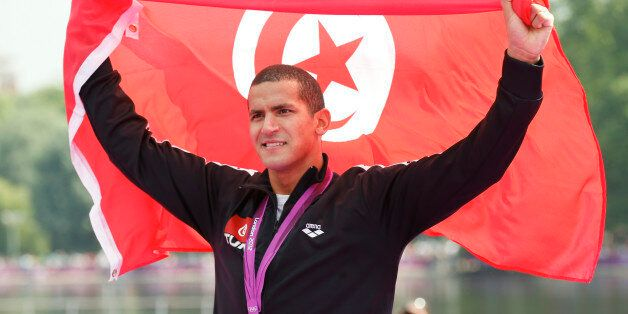Tunisia's Oussama Mellouli poses with his gold medal wrapped in national flag after the men's 10km marathon...