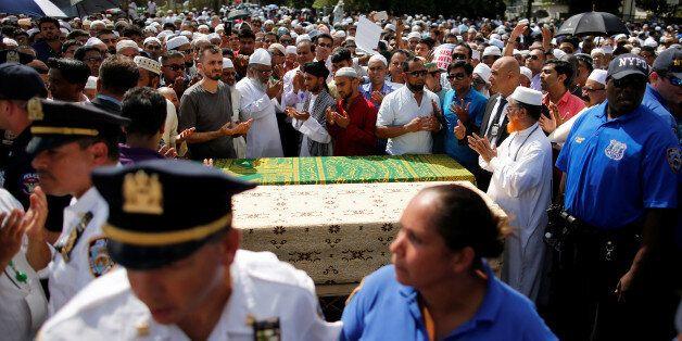 Des hommes prient autour des cercueils contenant les corps d'un imam et de son assistant tués par balles,...