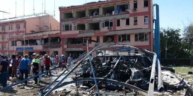 Turkish authorities search outside the damaged building of the police headquarters after an explosion...