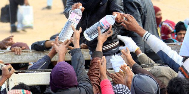 Evacuees receive bottles of water during food distribution at the UNHCR refugee camp near the border...
